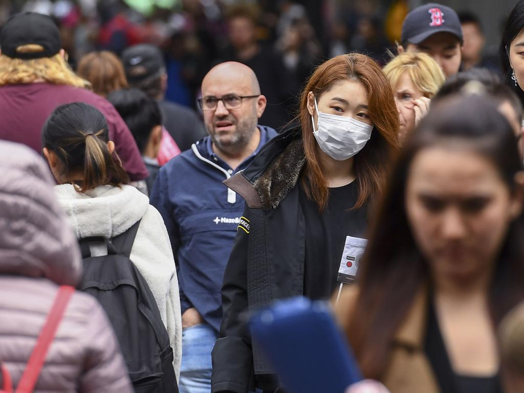 A woman wearing a face mask crosses the street in Melbourne. Wearing masks is still a rarity in Australia, as opposed to many Asian nations where it is much more prevalent. Picture: William WEST / AFP.