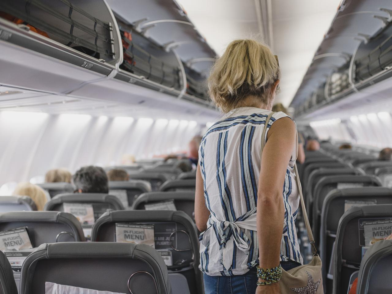 Mature woman is walking down the airplane aisle to her designated seat.