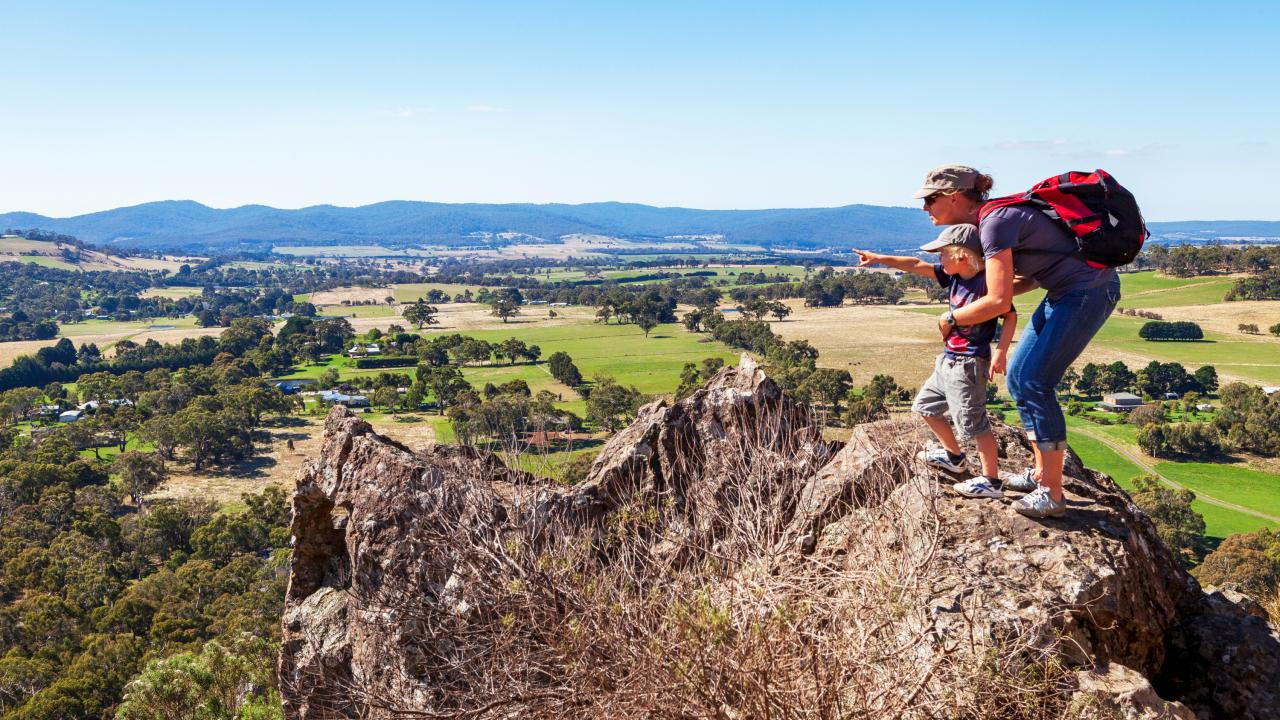 Mother and son look out over the Macedon Ranges farmland from the summit of Hanging Rock.