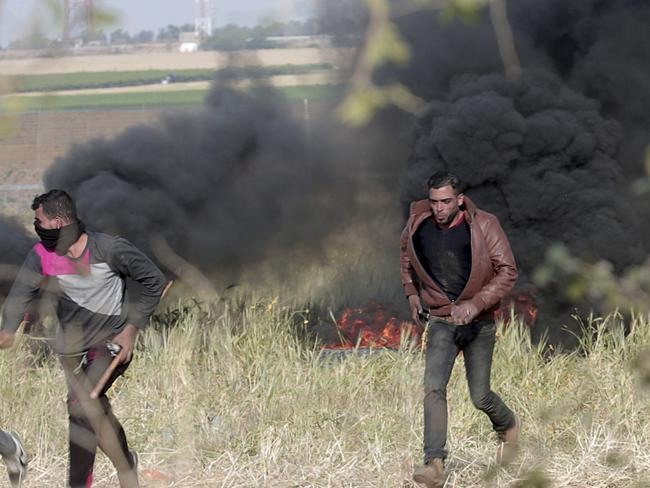 Protesters run to cover themselves from Israeli soldiers. Picture: AP Photo/Adel Hana
