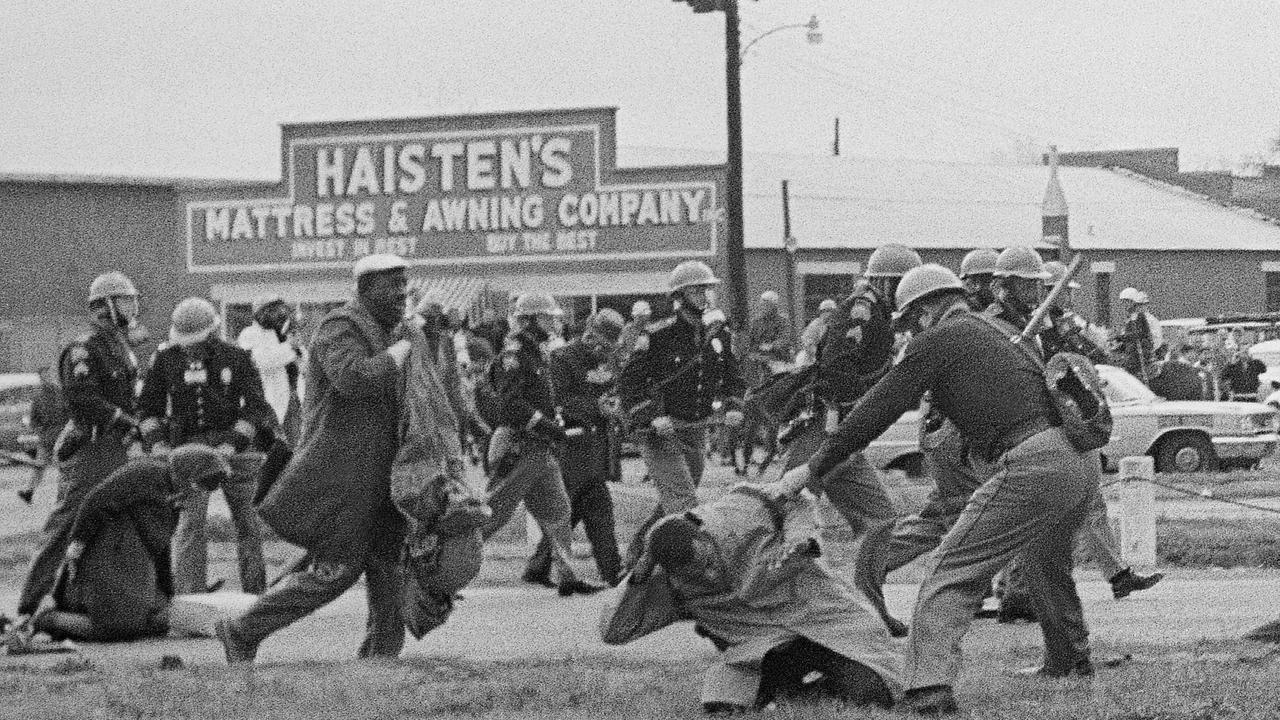 John Lewis was known for this iconic photo which captured a state trooper swining a billy club at him (pictured right foreground) in a bid to break up a civil rights voting march in Selma, Alabama. Lewis sustained a fractured skull. Picture: AP.