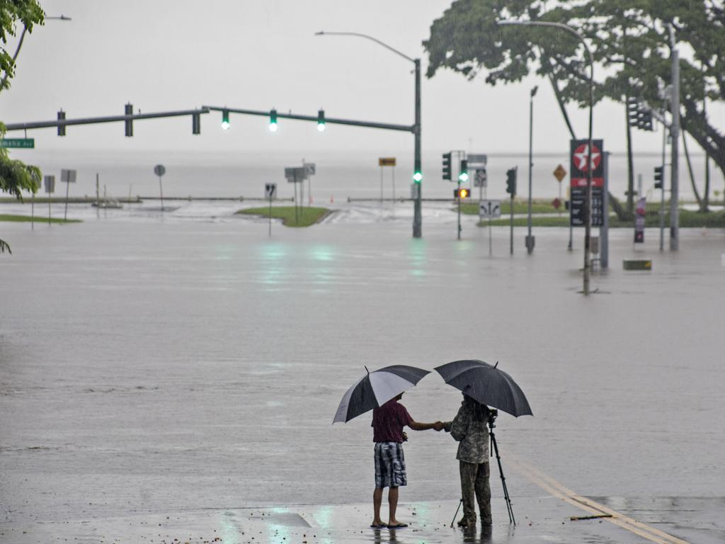In this 2018 photo, people stand near flood waters from Hurricane Lane in Hilo, Hawaii. Some of Hawaii could soon be underwater. Picture: Hawaii Tribune-Herald/AP