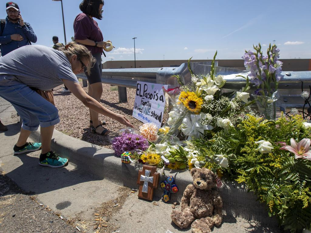 El Paso residents place flowers at a makeshift memorial for the victims of the mass shooting at a shopping complex in El Paso, Texas. Picture: AP