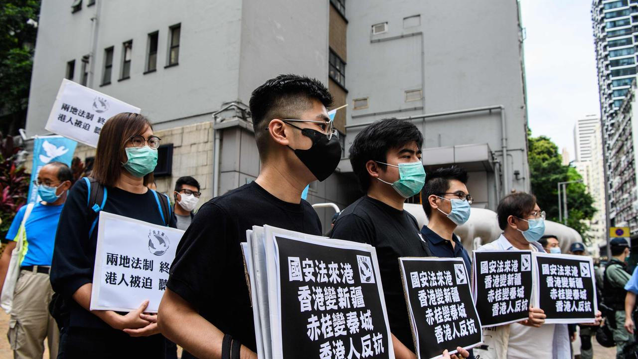 """Pro-democracy protesters hold placards that say """"Hong Kongers Revolt"""" as they march from outside the Western Police Station to the Chinese Liaison Office in Hong Kong. Picture: Anthony Wallace/AFP"""