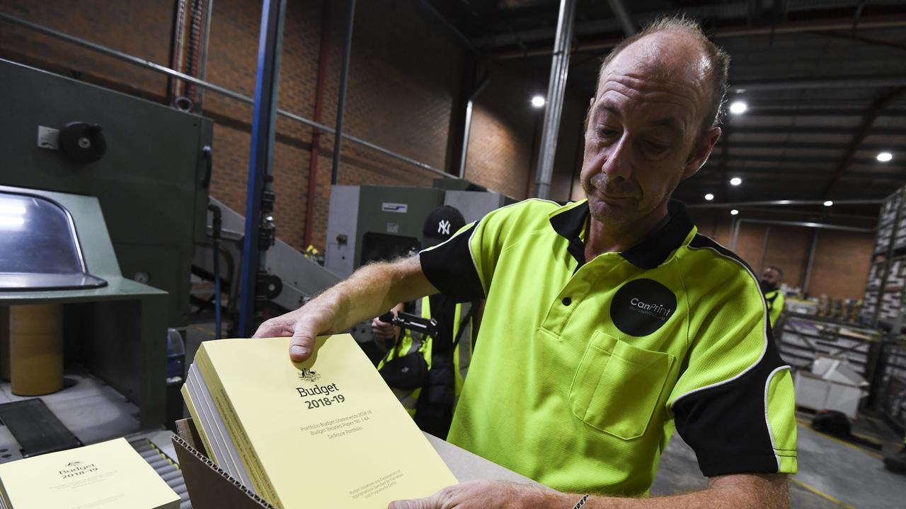 A print worker handling a stack of the 2018-19 Budget papers in Canberra. Picture: AAP Image/Lukas Coch.