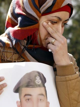 The wife of the Jordanian pilot holds a poster of him. Picture: Raad Adayleh