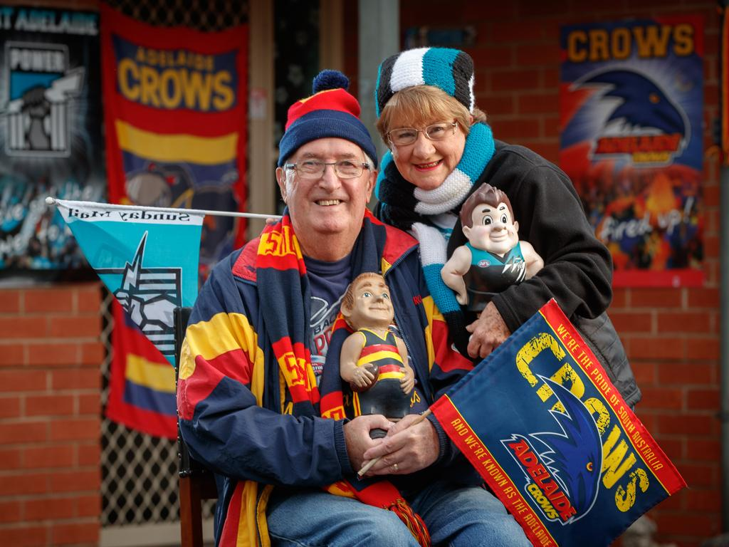 INTENSE RIVALRY: John and Susan Dearman with their Crows and Power dolls and gnomes in the Ridgehaven Rise Retirement Village. Picture: Matt Turner