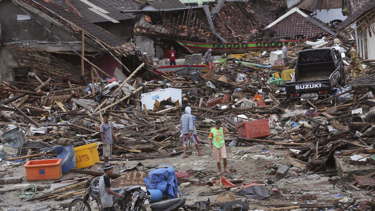 People inspect the damage at a tsunami-ravaged village in Sumur, Indonesia. Picture: AP