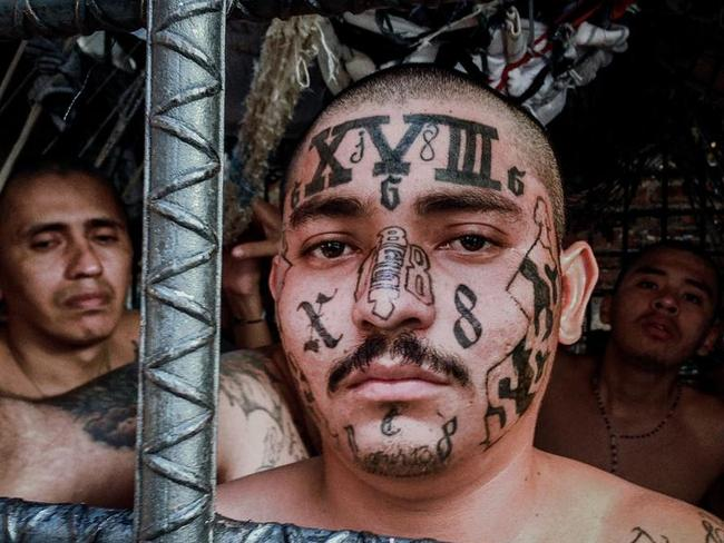 Gang violence ... M18 gang members look out through the bars of the designated M18 'gang cage' in the Quezaltepeque police station in San Salvador. Picture: Giles Clarke/Getty