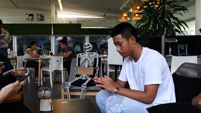 Patrons enjoy drinks next to a skeleton. Picture: AFP/Lillian Suwanrumpha