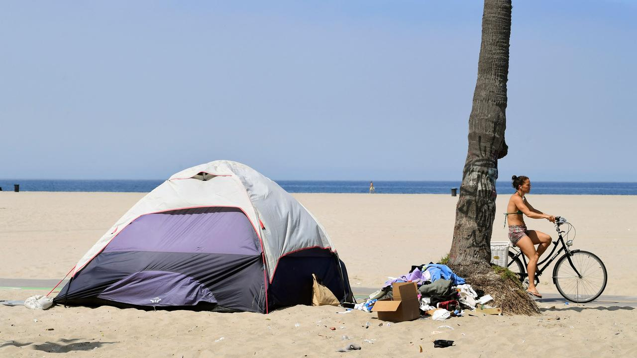A cyclist rides past a tent for the homeless on Venice Beach on June 30. A homeless encampment at Venice Beach on June 30. Picture: Frederic J. Brown / AFP