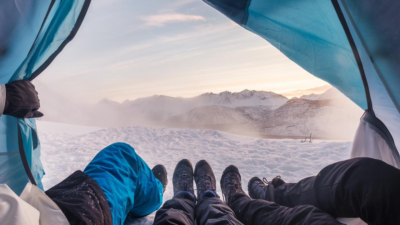 Group of climber are inside a tent with open for view of blizzard on snow mountain