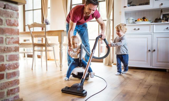 Father and two toddlers doing housework. Paternity leave.