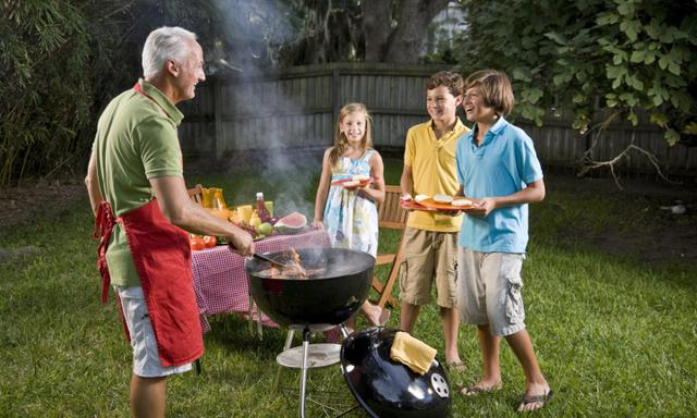 Father grilling hamburgers, hungry kids waiting