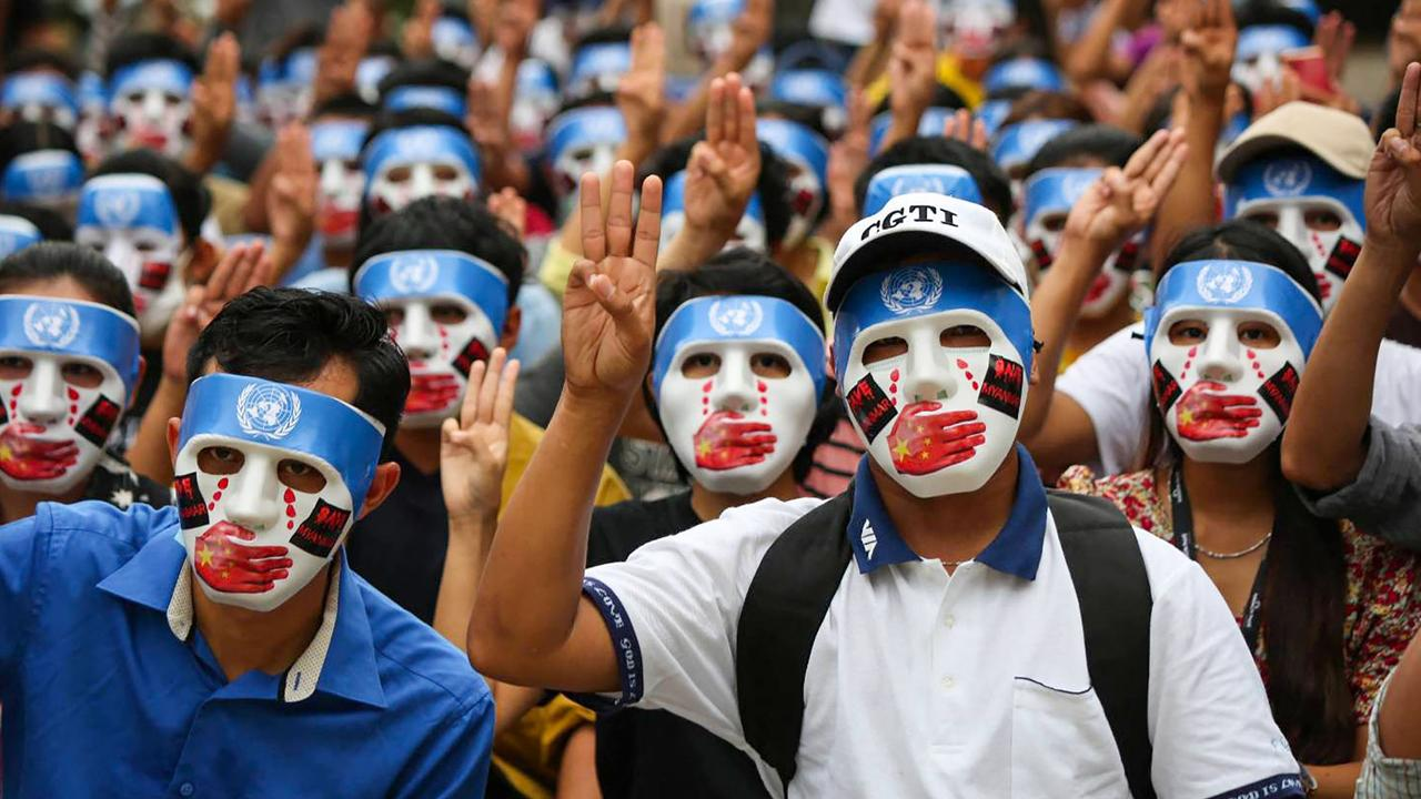 Protesters in Myanmar making the three-finger salute while wearing masks that express what they say is Chinese interference in the UN's handling of Myanmar affairs. Picture: AFP