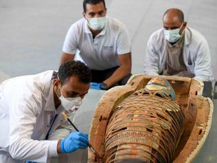 Archaeologists inspect a mummy, wrapped in a burial shroud adorned with brightly coloured hieroglyphic pictorials, during the unveiling of an ancient treasure trove of more than a 100 intact sarcophagi, at the Saqqara necropolis 30 kms south of the Egyptian capital Cairo, on November 14, 2020. - Egypt announced the discovery of an ancient treasure trove of more than a 100 intact sarcophagi, the largest such find this year. The sealed wooden coffins, unveiled on site amid fanfare, belonged to top officials of the Late Period and the Ptolemaic period of ancient Egypt. They were found in three burial shafts at depths of 12 metres (40 feet) in the sweeping Saqqara necropolis south of Cairo. (Photo by Ahmed HASAN / AFP)