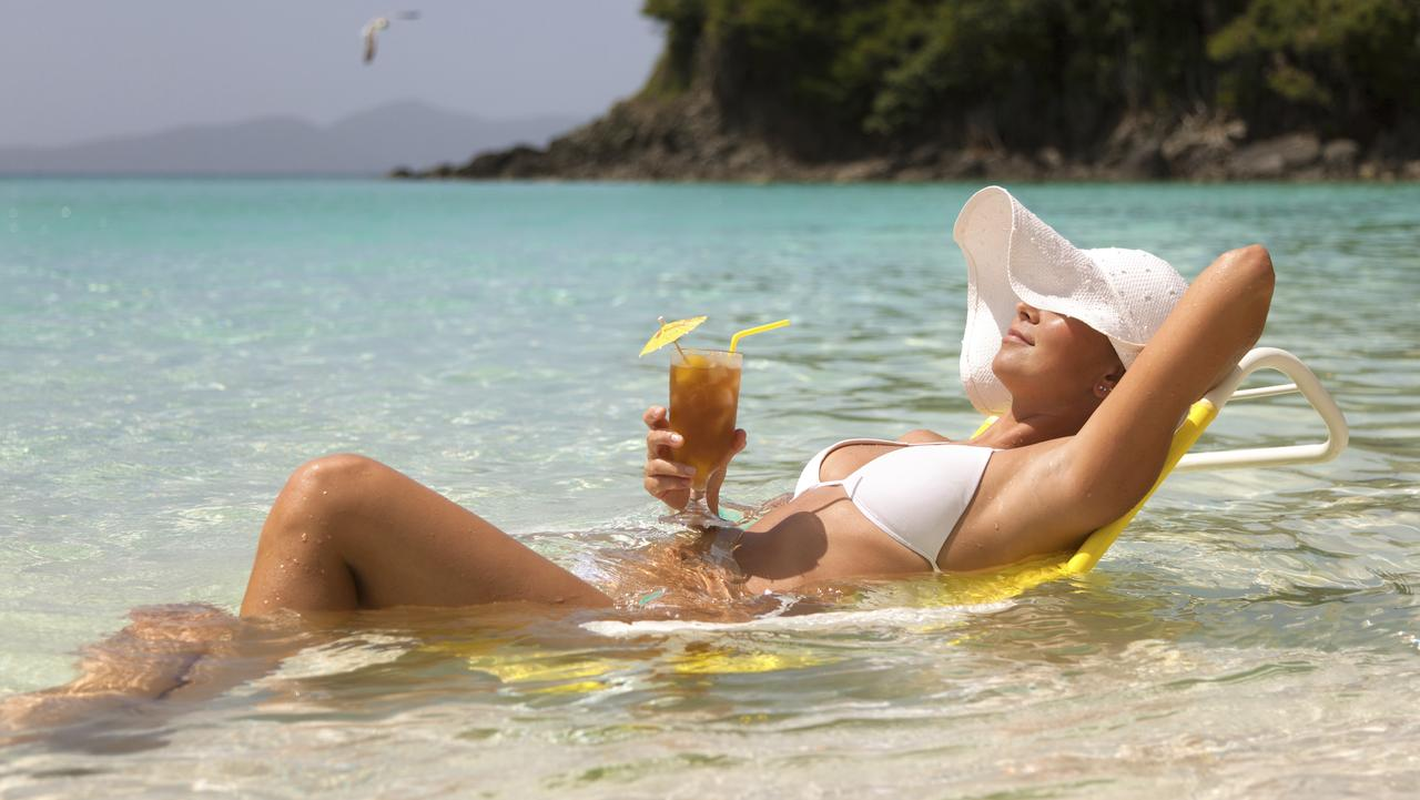 young woman in white bikini and summer hat relaxing in a beach chair in Caribbean waters and enjoying a tropical cocktail