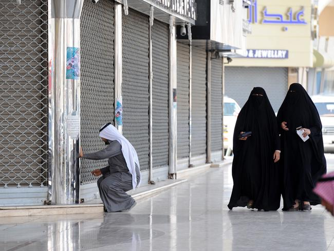 Saudi women walk past a jeweller arriving to open his shop in the Tiba gold market in the capital Riyadh on February 27, 2018. The Riyadh gold souk is short of salesmen after a government edict to replace foreign workers with Saudis as part of contentious efforts to tackle high unemployment, with many of them who have been long accustomed to a generous cradle-to-grave welfare system regard such jobs as degrading. / AFP PHOTO / Fayez Nureldine