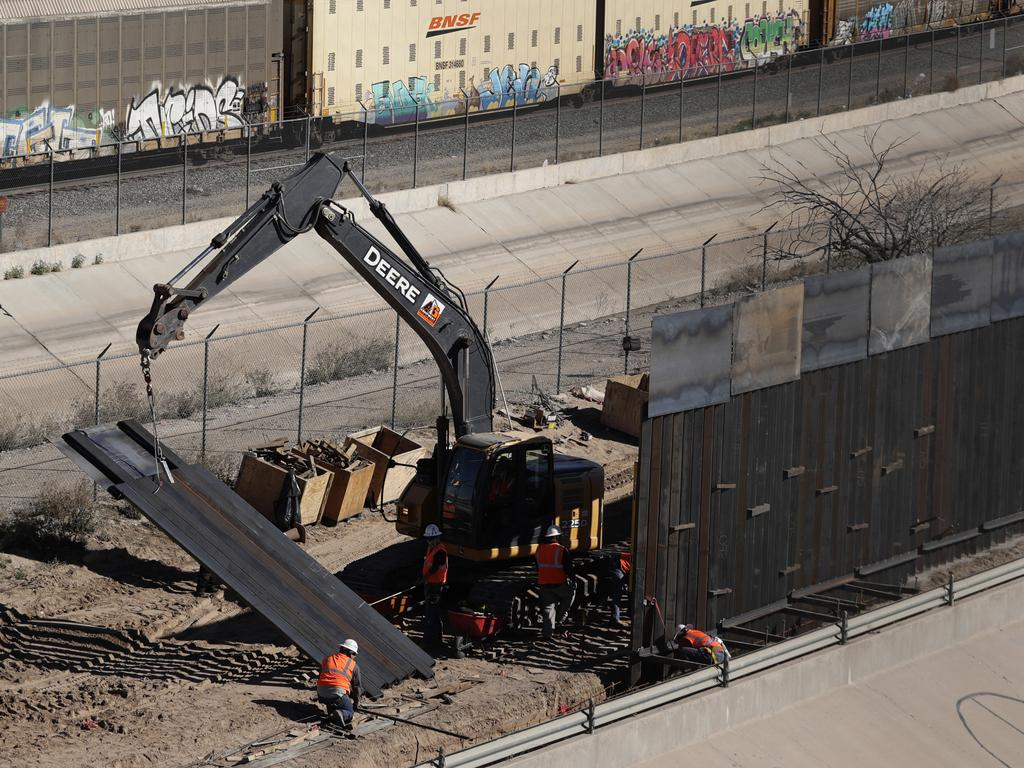 Workers place sections of a metal wall as a new barrier is built along the Texas-Mexico border near downtown El Paso. Photo: AP Photo/Eric Gay