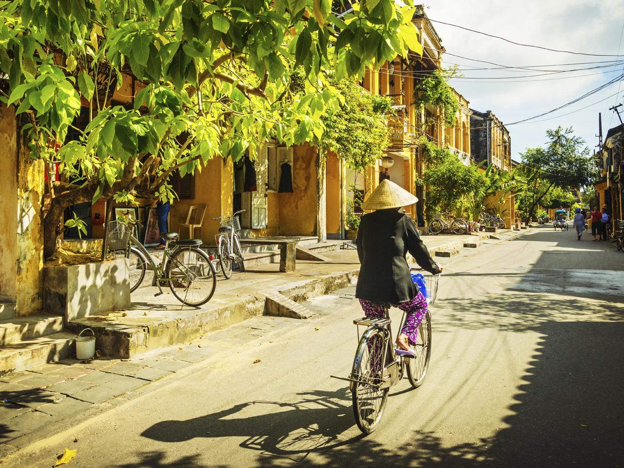 ESCAPE: DOC HOLIDAY  ..  Hoi An, Vietnam - November 21, 2012: Vietnamese woman with traditional Vietnamese hat on a bicycle rides down along the street. Picture: iStock