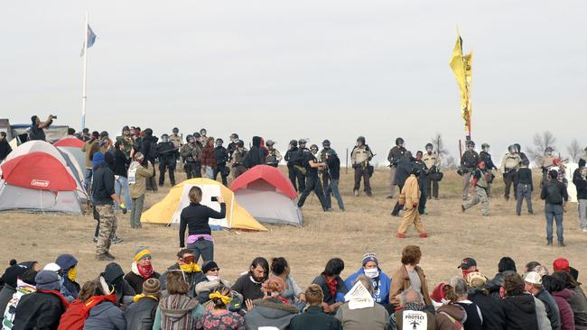 Dakota Access Pipeline protesters sit in a prayer circle at the Front Line Camp as a line of law enforcement officers make their way across the camp to remove the protesters. Picture: AP.