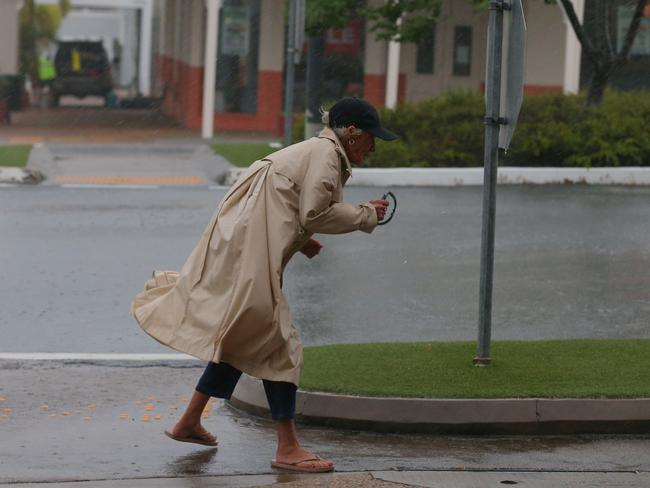 A brave or foolhardy local dashes out to take a quick look out to check the area in the main street. Picture: Lyndon Mechielsen/The Australian