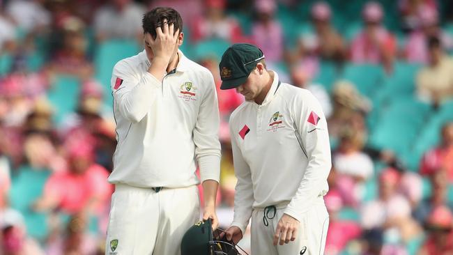 Australian captain Steve Smith looks at Matt Renshaw's helmet after Renshaw (left) copped a blow while fielding.