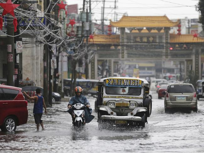 A passenger jeep navigates a flooded street caused by rains from Typhoon Nock-Ten in Quezon City, north of Manila.