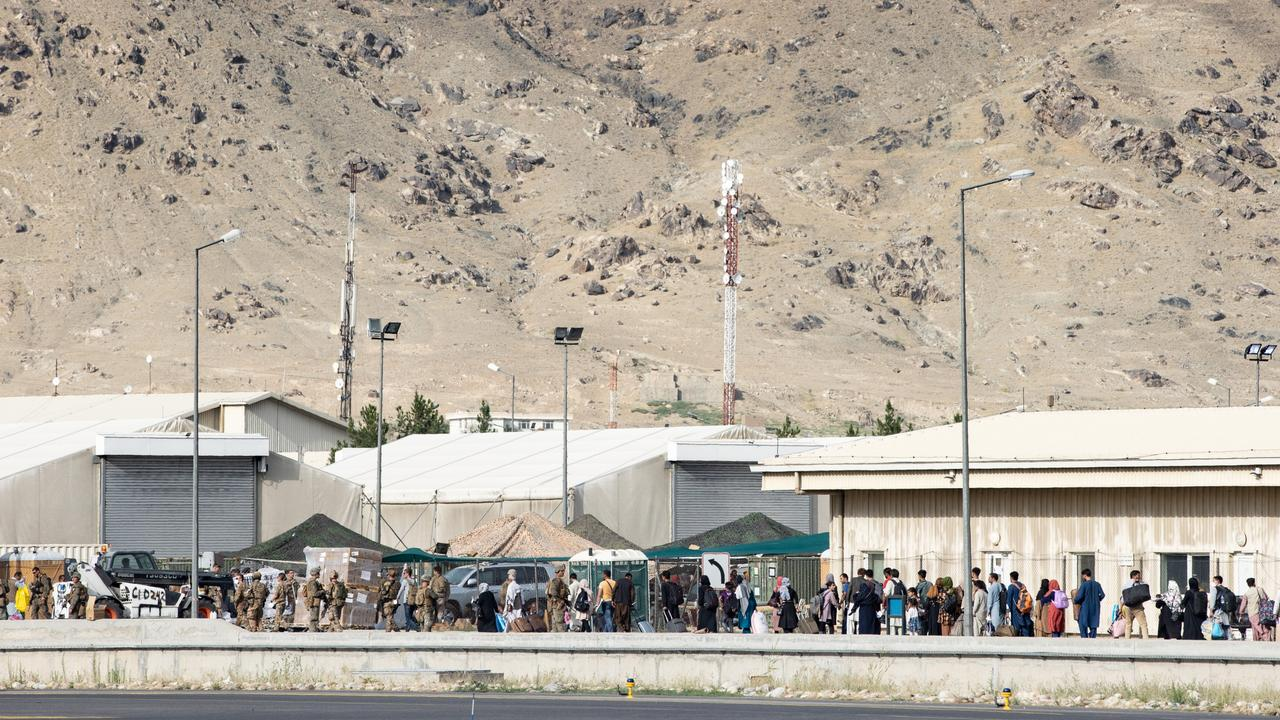 Australian citizens and visa holders form a line to depart Australia's military base in the Middle East.
