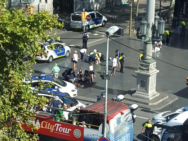 Injured are helped by responders. According to witnesses the white van swerved from side to side as it drove into tourists and residents. Picture: AP