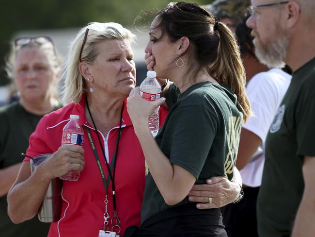 Santa Fe High School staff were emotional as they gathered in petrol station car park after the shooting. Picture: Jennifer Reynolds/The Galveston County Daily News via AP