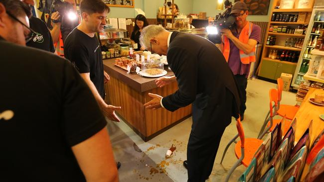 The Prime Minister drops his espresso coffee at Sydney fish markets on Wednesday. Picture: Rohan Kelly