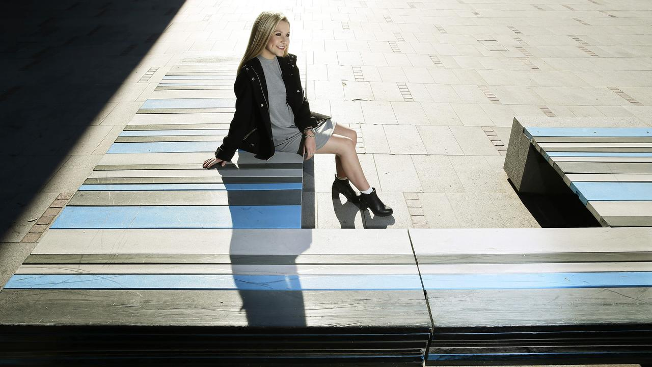 Sydney University student Eliza Ronan sits on one a REDcycle bench, made from recycled plastic. Picture: John Appleyard