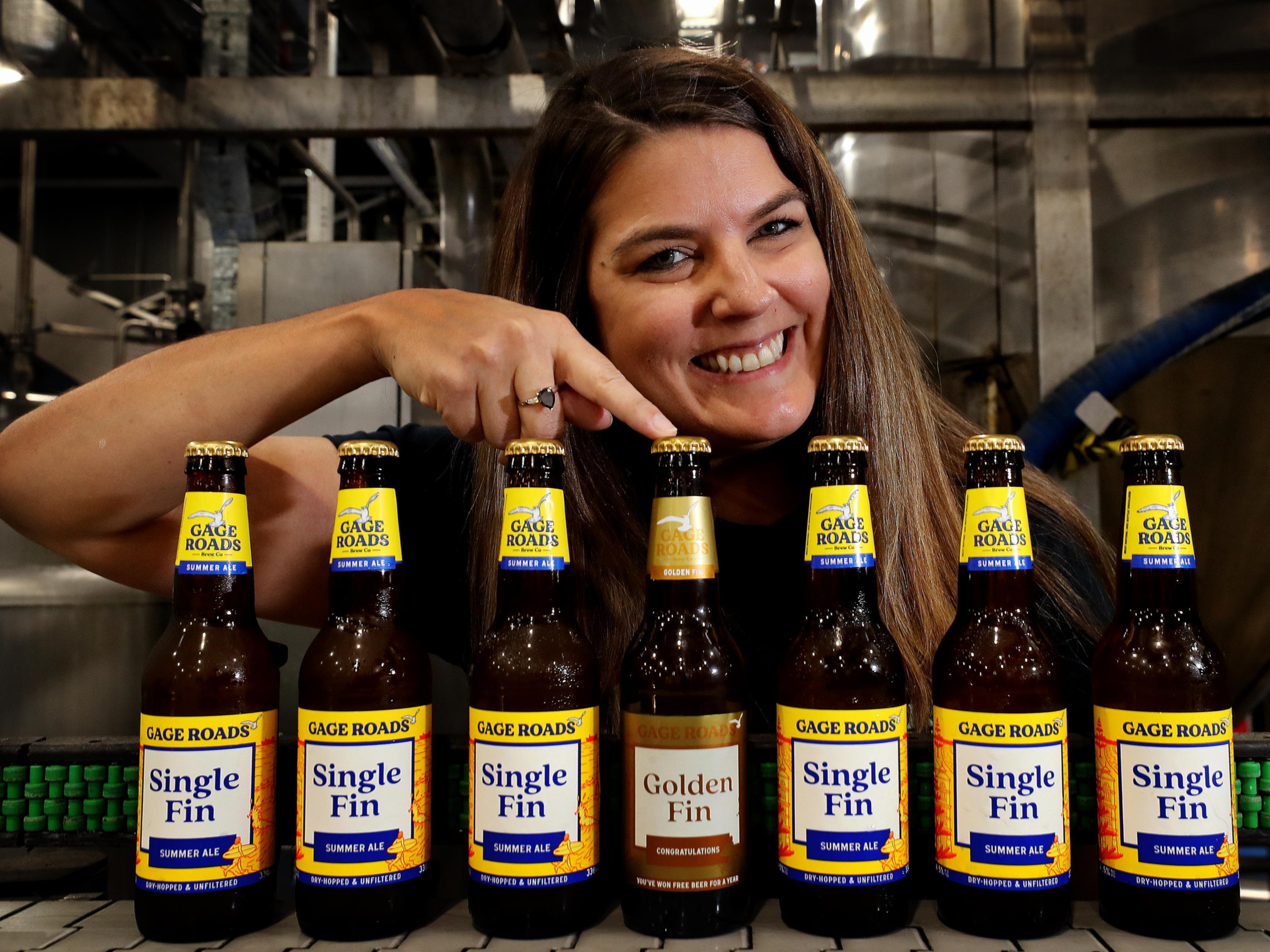 Gage Roads Brewing Company brand leader Bec Lauchlan with a bottle of Golden Fin.