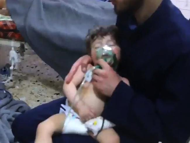 A volunteer holds an oxygen mask over a child's face at a hospital following a reported chemical attack on the rebel-held province of Eastern Ghouta. Picture: AFP