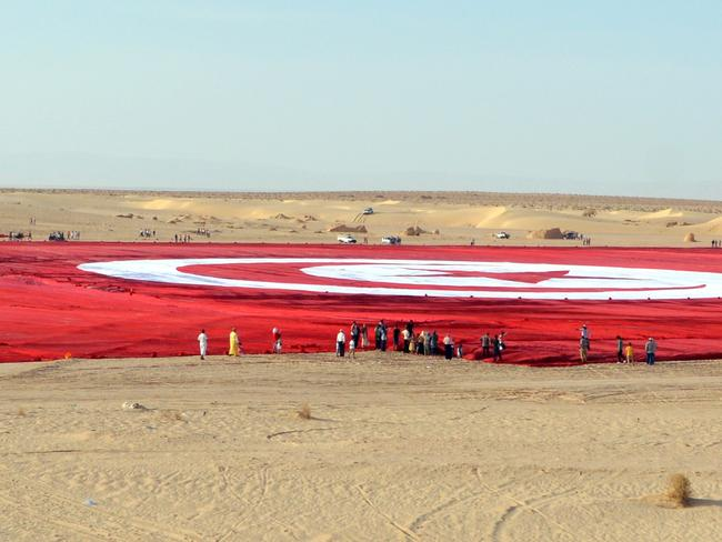 Tunisians have unfurled a national flag the size of 19 football pitches in a bid to set a Guinness world record and promote patriotism in the face of Islamist extremism.