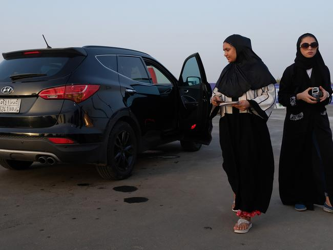 Women leave a station where she sat in a car while an instructor demonstrated a parking technique during an outdoor educational driving event for women. Pic: Getty