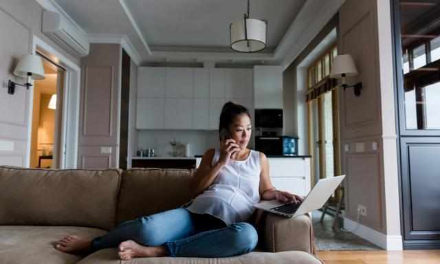 Pregnant woman talks on smartphone and uses a laptop while relaxing on a sofa in her home or apartment.