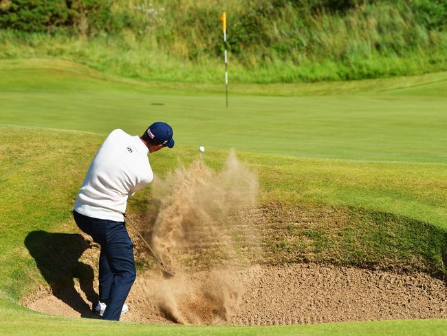 Adam Scott hits a bunker shot on the 13th hole.