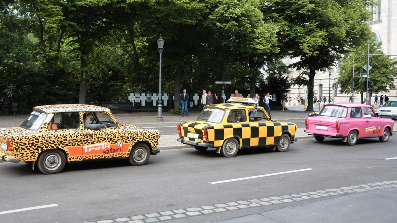 Tourists on a sightseeing tour in Trabants to the main attractions in Berlin.