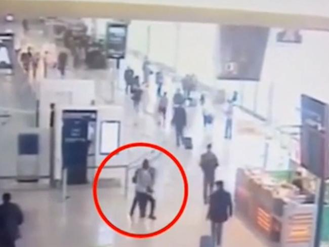 The moment an extremist grabs a female soldier from behind before being shot dead after a three-minute standoff at a Paris airport. Picture: AP.