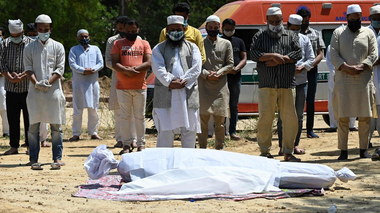 Relatives and friends pray during funeral of coronavirus victim at a graveyard in New Delhi. Picture: AFP