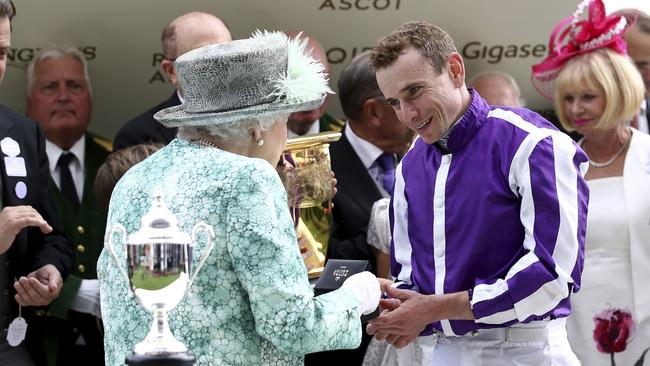 Britain's Queen Elizabeth II presents a medal to jockey Ryan Moore after he rode Merchant Navy to victory in the Diamond Jubilee Stakes.