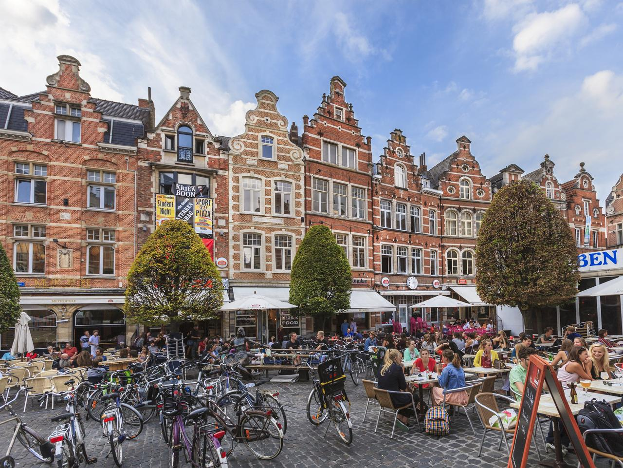 "Leuven, Belgium - September 15, 2014: Students sit at the outdoor tables of the Oude Markt, a large rectangular square also known as the ""longest bar in the world"". It is bordered by restaurants, bar and pubs, and is the meeting point of the numerous students living in the city."