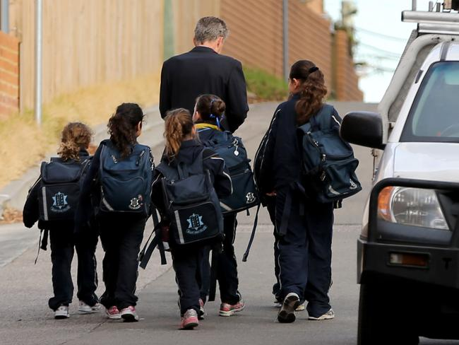 The Mount Sinai College principal Phil Roberts escorts students from the bus. Picture: John Grainger