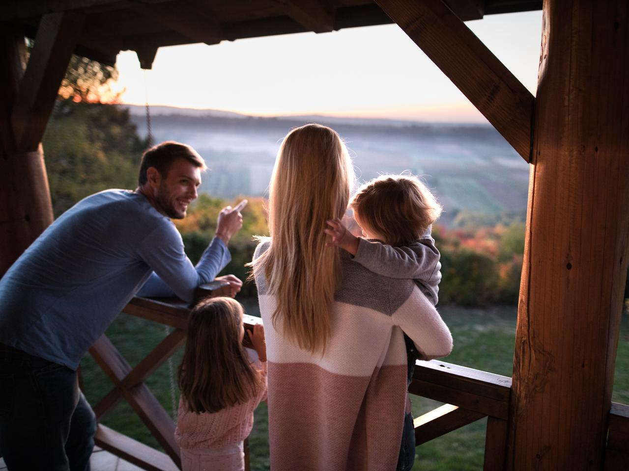 Family standing together on a balcony while father is pointing at distance. Focus is on mother and son.