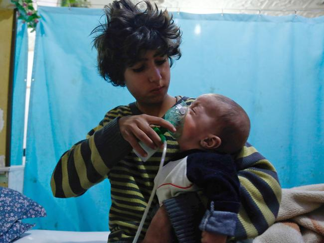 A Syrian boy holds an oxygen mask over the face of an infant at a makeshift hospital following a reported gas attack on the rebel-held besieged town of Douma. Picture: AFP