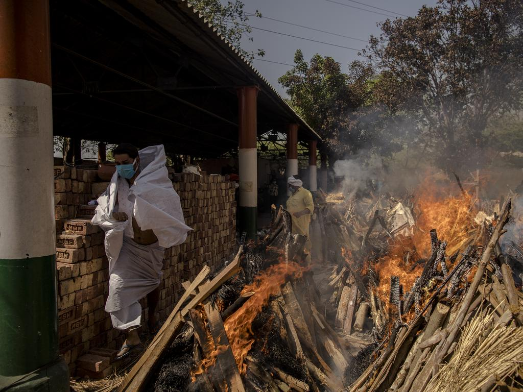A priest runs to avoid the heat from the multiple burning funeral pyres of patients who died of the COVID-19 coronavirus disease at a crematorium in New Delhi, India. Picture: Anindito Mukherjee/Getty Images