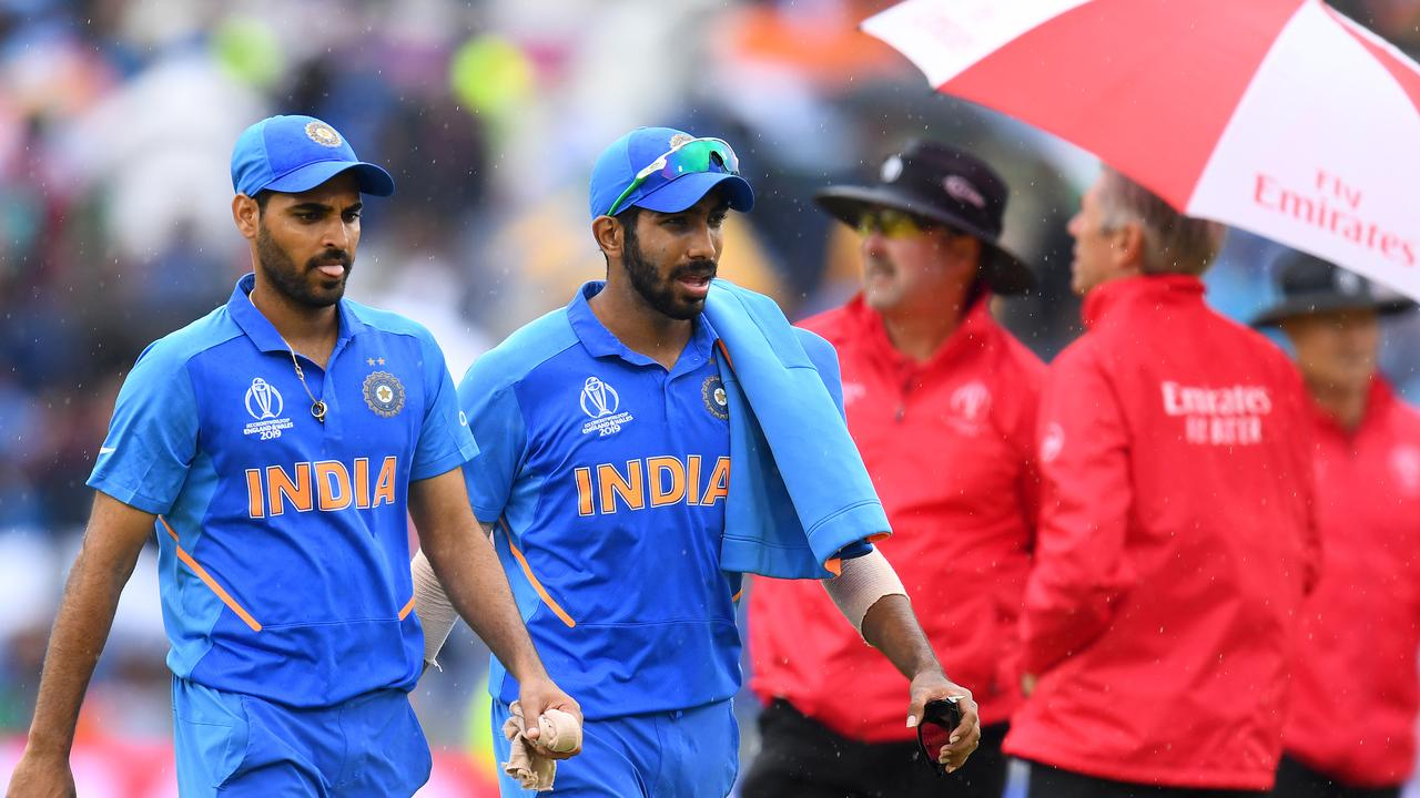 Bhuvneshwar Kumar and Jasprit Bumrah leave the pitch as rain halts play. Picture: Getty