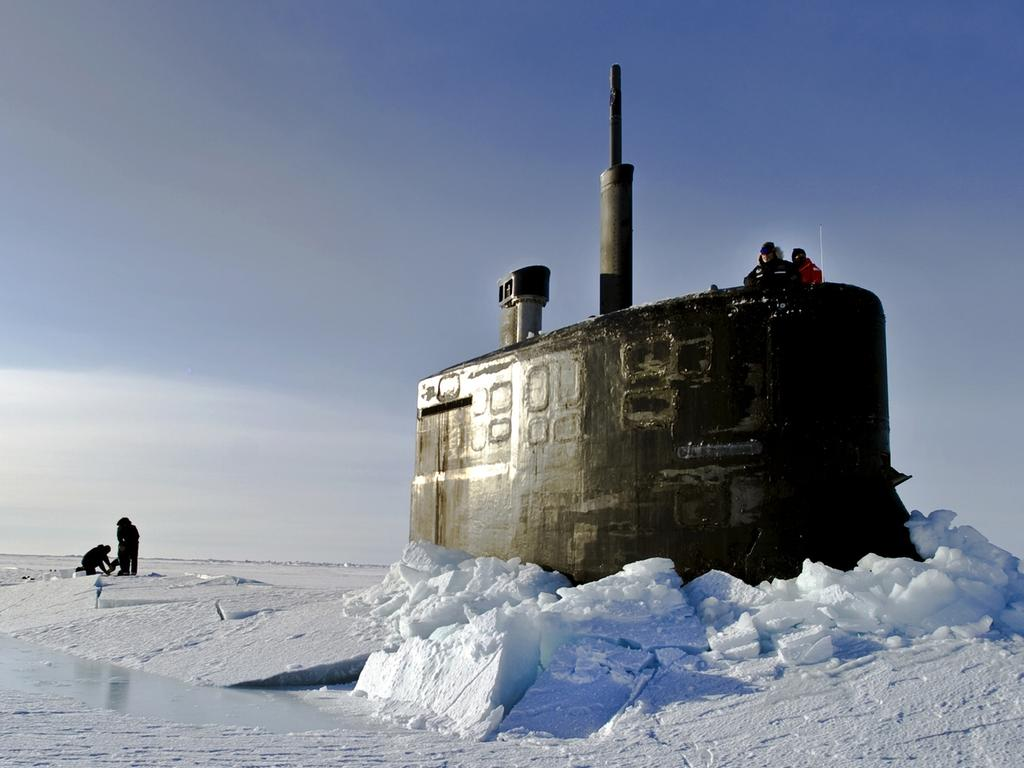 Arctic Ocean, March 19, 2011 - Sailors and members of the Applied Physics Laboratory Ice Station clear ice from the hatch of the Seawolf-class submarine USS Connecticut (SSN-22) as it surfaces above the ice during ICEX 2011.